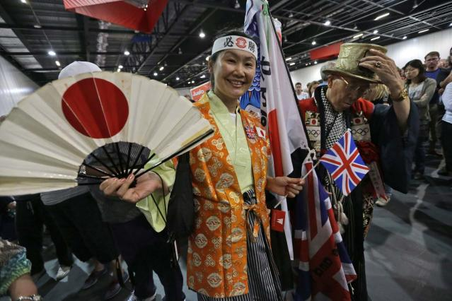 Supporters of the Japanese judo team pose for photos in the judo venue of the ExCel Centre at the 2012 Summer Olympics, Saturday, July 28, 2012, in London. (AP Photo/Ng Han Guan)