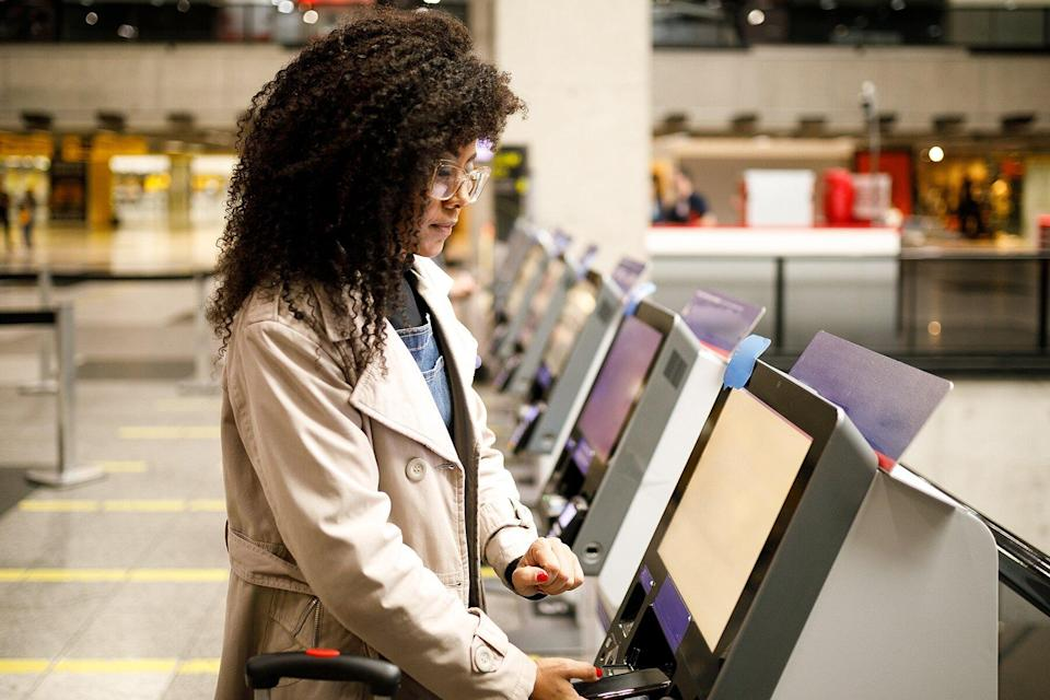 Woman doing self check in at the airport with mobile phone