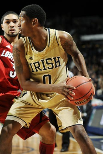 Notre Dame guard Eric Atkins, right, attempts to drive to the basket as Louisville guard Peyton Siva defends during the first half of an NCAA college basketball game, Saturday, Feb. 9, 2013, in South Bend, Ind. (AP Photo/Joe Raymond)