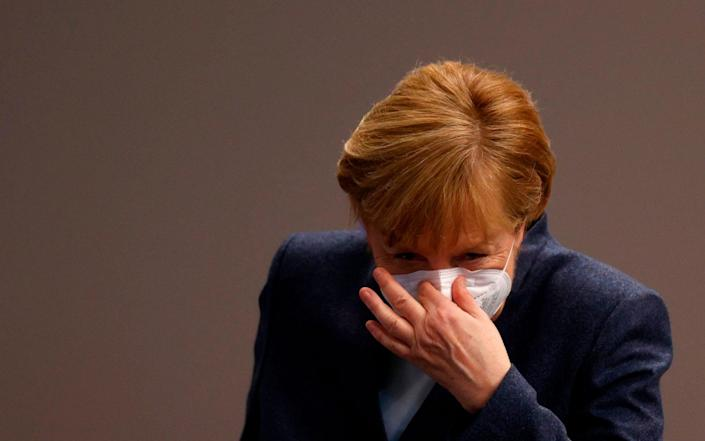 """(FILES) In this file photo taken on December 16, 2020 German Chancellor Angela Merkel puts her face protection mask on after a session of the Bundestag (lower house of parliament) in Berlin, amid the coronavirus Covid-19 pandemic. - Chancellor Angela Merkel on January 16, 2021 said significantly tougher measures were needed to slow Germany's coronavirus infections, party sources told AFP. Speaking at a meeting with top brass from her centre-right CDU party, Merkel said """"the virus can only be stopped with significant additional efforts"""", participants told AFP, adding that the chancellor wanted to hold fresh crisis talks with regional leaders next week. (Photo by Odd ANDERSEN / AFP) (Photo by ODD ANDERSEN/AFP via Getty Images) - ODD ANDERSEN/AFP"""