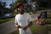"Demarkio Pritchett, 29, stands with his daughter Mariah Pritchett 8, playing in the background outside his grandmother's home, Tuesday, Oct. 6, 2020, in Meridian, Miss. Pritchett, who said he was convicted as a teenager of drug possession ""and some other stuff,"" can't vote in Mississippi for the rest of his life. Anyone convicted here of one of 22 crimes, from murder to felony shoplifting has their voting rights permanently revoked. Pritchett's only chance: getting a pardon from the governor, or convincing two-thirds of the state's lawmakers to pass a bill written just for him. (AP Photo/Wong Maye-E)"