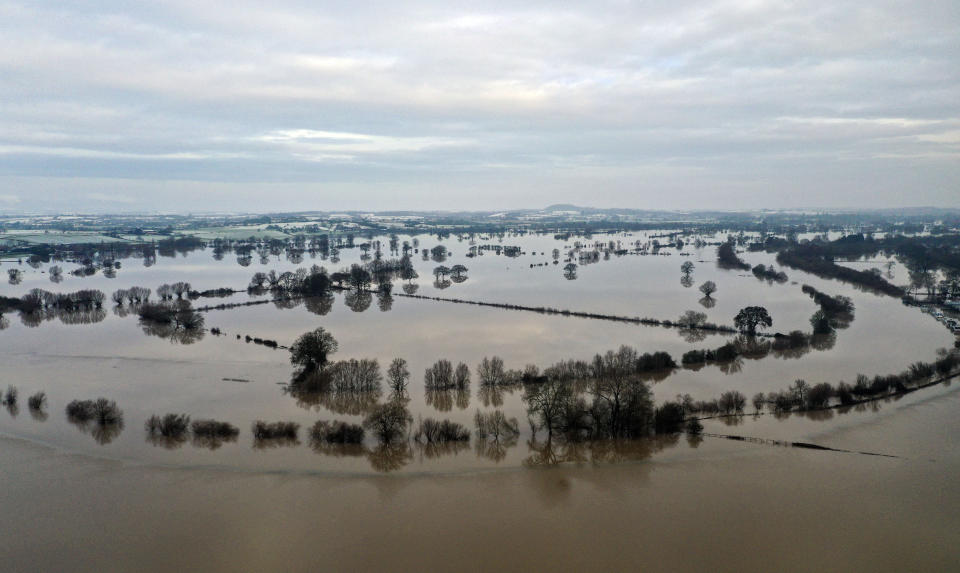 Fields remain flooded after the River Severn broke its banks near Apperley, England, Tuesday Dec. 29, 2020.  In the aftermath of Storm Bella some flood warnings are still in place although cold weather has bought snow and ice to some areas. (Steve Parsons/PA via AP)