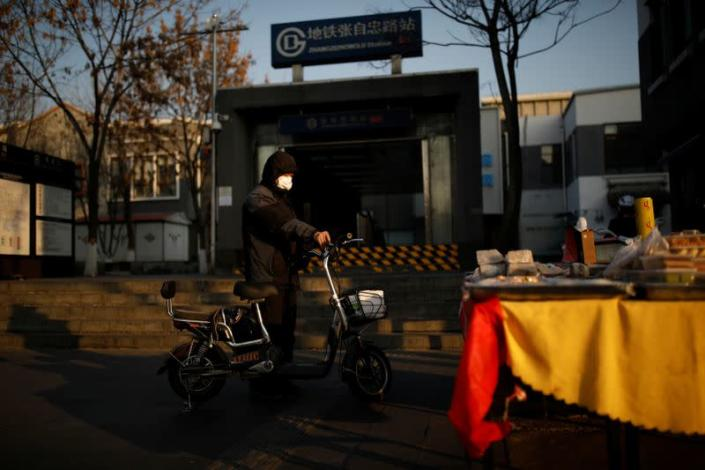 A man wearing a face mask stands next to his scooter outside a subway station as the country is hit by an outbreak of the new coronavirus, in Beijing