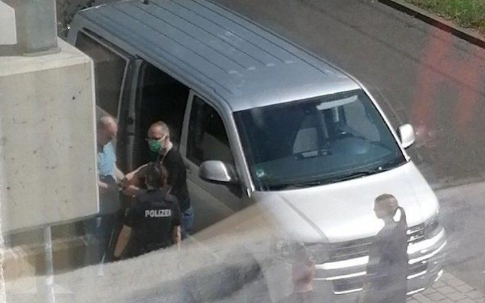 British national David Smith being handcuffed and led into an unmarked van by police on Tuesday afternoon - Henry Bodkin