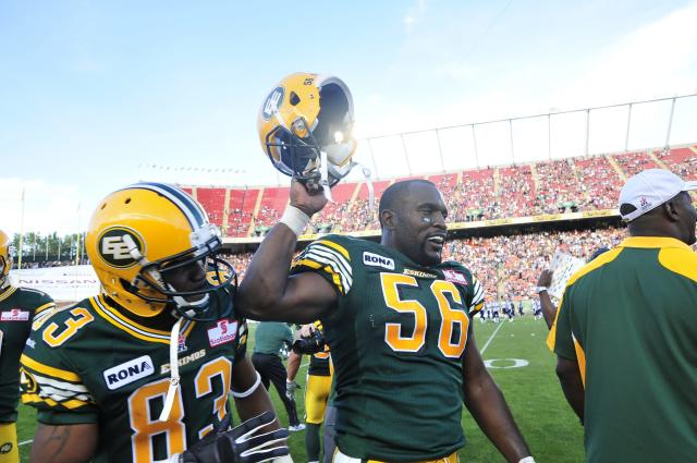 left to right - Edmonton Eskimos player # 56 ( DL) Lee Robinson celebrates with the other players on the Eskimos sidelines at the end of the 4th quarter of CFL game action between the Edmonton Eskimo's and the Toronto Argonauts at Commonwealth stadium in Edmonton June 30/2012 (CFL PHOTO / Walter Tychnowicz)