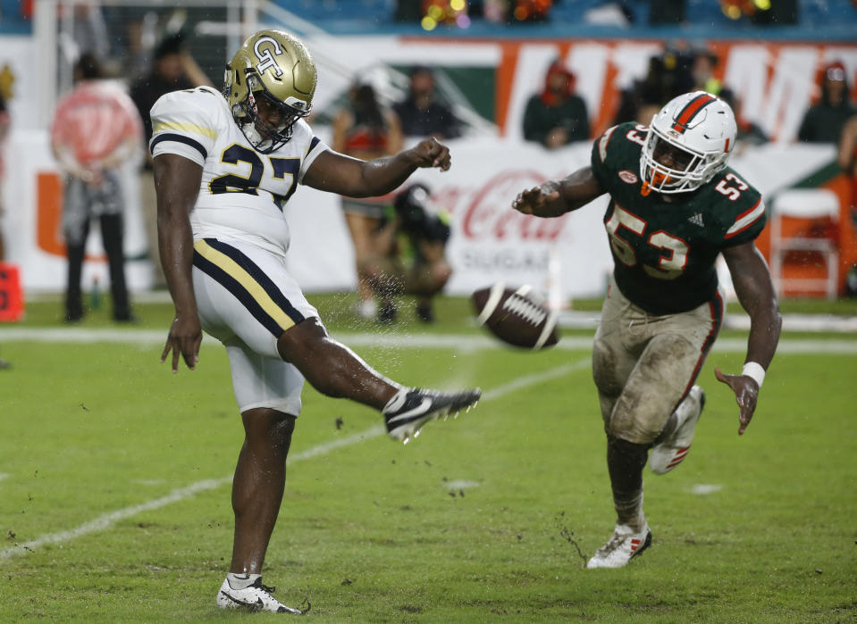 FILE - In this Oct. 14, 2017, file photo, Georgia Tech punter Pressley Harvin III (27) kicks the ball as Miami linebacker Zach McCloud (53) attempts to block during the second half of an NCAA college football game in Miami Gardens, Fla. Harvin, who packs 263 pounds on his 6-foot frame, set school and ACC single-season records last year with a 48-yard net punting average. He can throw the football just as far and as accurately as he can punt it. (AP Photo/Wilfredo Lee, File)