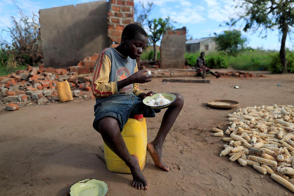 Bernado Jofresse, 14, eats rice for breakfast as he sits beside his family's damaged house. (Photo: Zohra Bensemra/Reuters)