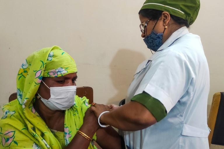 A sex worker (L) from Bangladesh's largest brothel receives a dose of a Covid-19 vaccine in Daulatdia