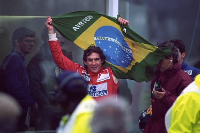 Senna flying the Brazilian flag as he works his way through the crowd to the winner's podium after victory in the European Grand Prix at Donington Park (David Jones/PA)