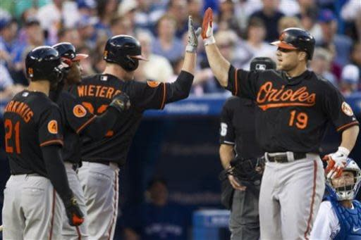 Baltimore Orioles' Chris Davis, right, is congratulated by Matt Wieters, center, Adam Jones, center left, and Nick Markakis after hitting a three-run homer as Toronto Blue Jays catcher Josh Thole looks on during the sixth inning of a baseball action in Toronto on Friday, June 21, 2013. (AP Photo/The Canadian Press, Chris Young)