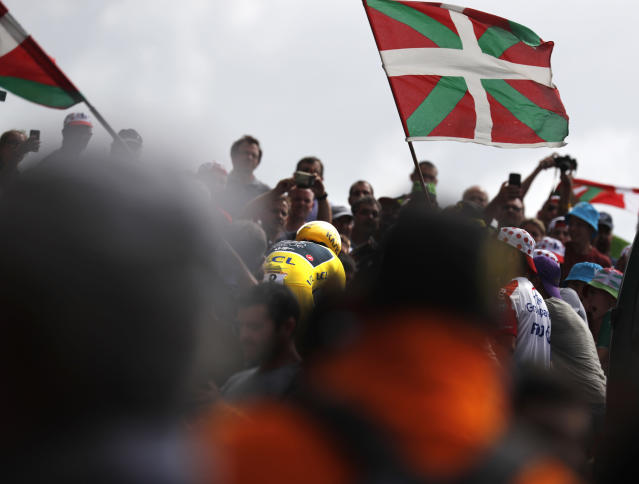 Spectators wave Basque flags as Britain's Geraint Thomas, wearing the overall leader's yellow jersey, center, rides during the twentieth stage of the Tour de France cycling race, an individual time trial over 31 kilometers (19.3 miles)with start in Saint-Pee-sur-Nivelle and finish in Espelette, France, Saturday July 28, 2018. (AP Photo/Peter Dejong)