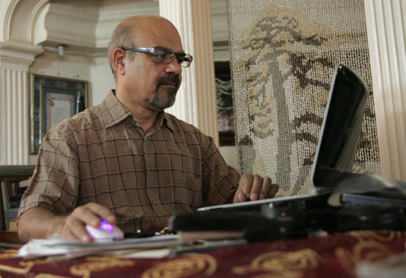 In this Monday, Aug. 6, 2012 photo, Iranian pilot Hooshang Shahbazi checks the internet at his home in Tehran, Iran. Shahbazi, who guided an Iran Air Boeing passenger plane to a safe emergency landing last year has launched an individual campaign to lift Western sanctions that restrict the import of civilian plane spare parts. (AP Photo/Vahid Salemi)