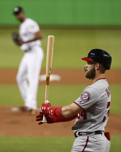 Washington Nationals' Bryce Harper, foreground, prepares to bat against Miami Marlins starting pitcher Sandy Alcantara, rear, during the first inning of a baseball game, Tuesday, Sept. 18, 2018, in Miami. (AP Photo/Wilfredo Lee)