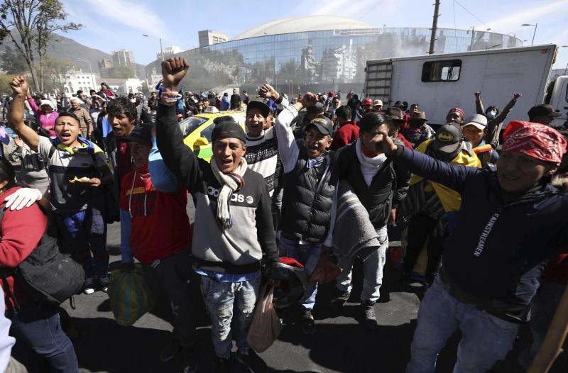 Anti-government protesters cheer as they wait for a bus to return them home, in the aftermath of violent protests against the government, in Quito, Ecuador, Monday, Oct. 14, 2019. Ecuador celebrated a deal President Lenín Morenoand indigenous leaders struck late Sunday to cancel a disputed austerity package and end nearly two weeks of protests that have paralyzed the economy and left seven dead.(AP Photo/Fernando Vergara)
