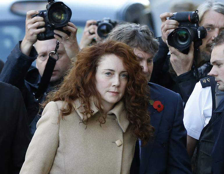 Former newspaper editor Rebekah Brooks and husband Charlie Brooks, obscured behind right, arrive at The Old Bailey law court in London, Monday, Oct. 28, 2013. Former News of the World national newspaper editors Rebekah Brooks and Andy Coulson are due to go on trial Monday, along with several others, on charges of hacking phones and bribing officials while at the now closed tabloid paper.(AP Photo/Kirsty Wigglesworth)