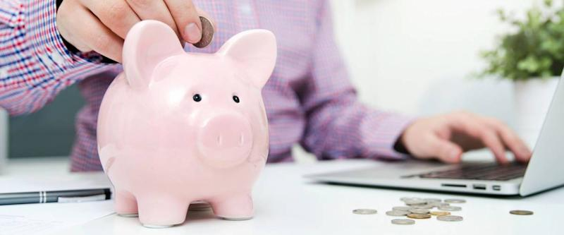Man putting coin into a piggy bank, while sitting at his computer