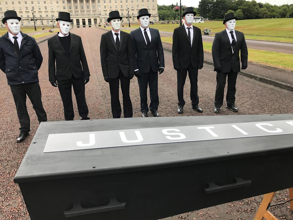 Protesters line up behind a coffin bearing the word 'justice' (Jonathan McCambridge/PA)