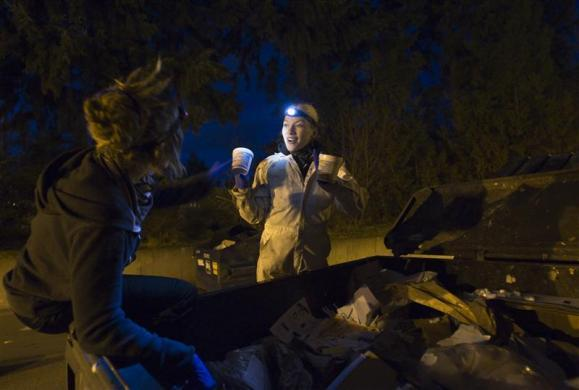 Anna-Rae Douglass (L), 23, and Robin Pickell, practicing 'freegans,' react to finding food in a dumpster behind an organic grocery store in Coquitlam, British Columbia April 5, 2012.