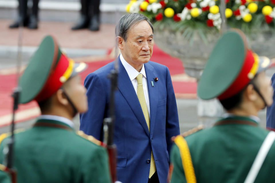 Japanese Prime Minister Yoshihide Suga reviews an honor guard at the Presidential Palace in Hanoi, Vietnam Monday, Oct. 19, 2020. Suga is on an official visit to Vietnam. (AP Photo/Minh Hoang, Pool)