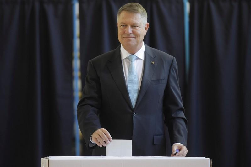 Incumbent candidate Klaus Iohannis smiles as he casts his ballot in the first round of a presidential election