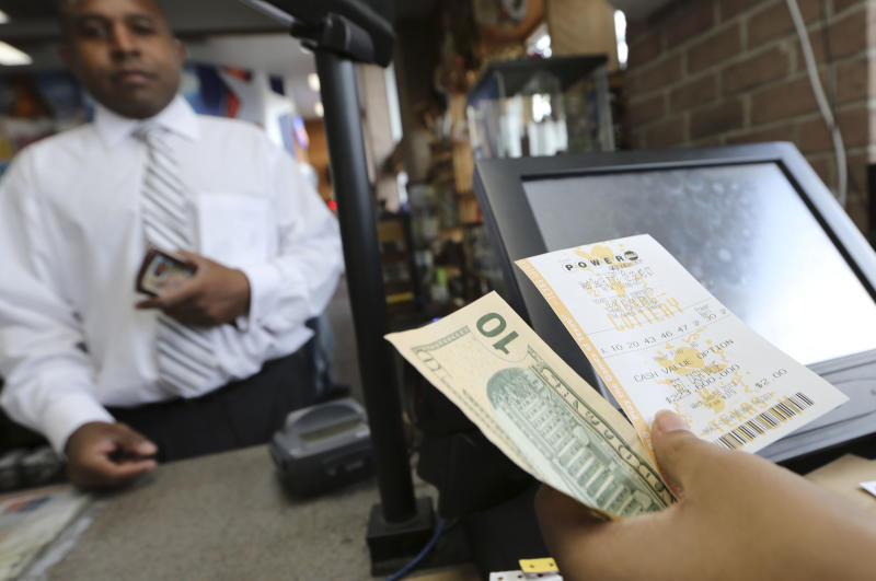 Larry McKinney, left, waits for his Powerball lottery ticket purchased at the Fuel City store in Dallas on Wednesday, Sept. 18, 2013. For Wednesday's drawing, Powerball's estimated $400 million jackpot will be the nation's fifth-largest ever. (AP Photo/LM Otero)