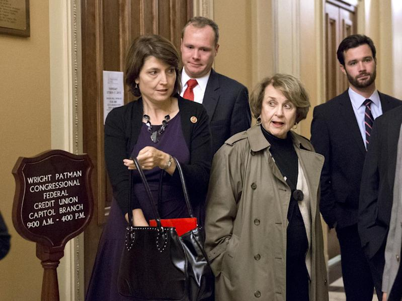 Rep. Cathy McMorris Rodgers, R-Wash., head of the Republican Conference, left, squeezes past Rep. Louise Slaughter, D-N.Y., the top Democrat on the House Rules Committee, at the end of the night after a planned vote in the House of Representatives collapsed, Tuesday, Oct. 15, 2013, at the Capitol in Washington. Time growing desperately short, House Republicans pushed for passage of legislation late Tuesday to prevent a threatened Treasury default, end a 15-day partial government shutdown and extricate divided government from its latest brush with a full political meltdown. (AP Photo/J. Scott Applewhite)
