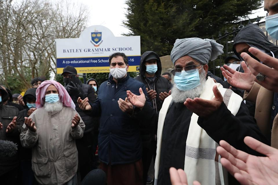 <p>Protesters take part in a prayer outside Batley Grammar School in Batley, West Yorkshire</p> (PA)