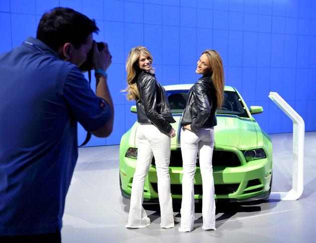 Models Lindsey Rae (L) and Lynsey Ramade pose with a Ford Mustang Boss 302 during the final press preview day for the North American International Auto Show in Detroit, Michigan, January 10, 2012. REUTERS/Mike Cassese