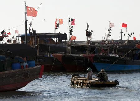 A dinghy ferries people to fishing boats at a port in the city of Dongfang on the western side of China's palm-fringed island province of Hainan, June 18, 2014.REUTERS/John Ruwitch
