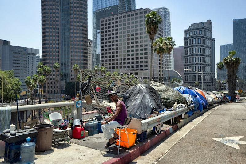 A homeless man sits at his tent along the Interstate 110 freeway in downtown Los Angeles. California Gov. Gavin Newsom met with the mayors of some of California's largest cities to discuss the homeless situation last month.
