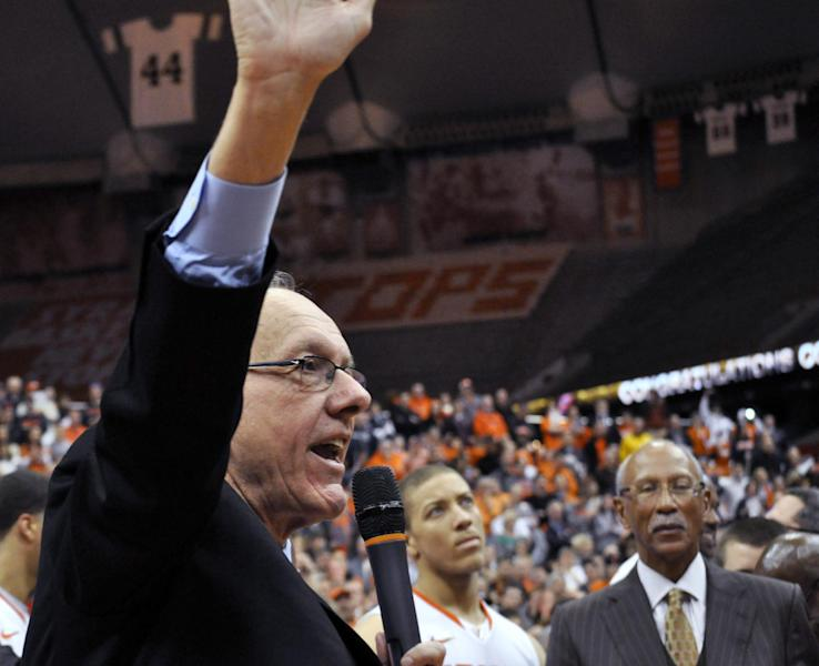 Syracuse coach Jim Boeheim acknowledges the crowd as Detroit Mayor Dave Bing, right, watches after Syracuse defeated Detroit 72-68 for Boeheim's 900th career victory in an NCAA college basketball game in Syracuse, N.Y., Monday, Dec. 17, 2012. Bing and Boeheim were roommates and teammates in college. (AP Photo/Kevin Rivoli)