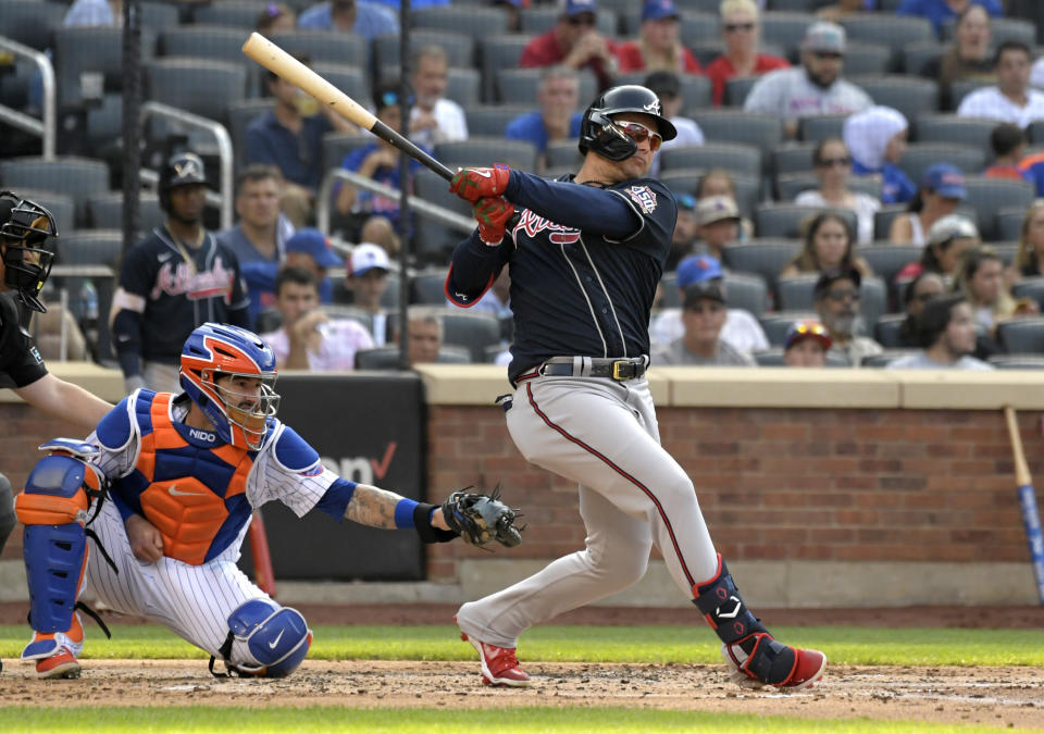 Atlanta Braves' Joc Pederson, right, hits an RBI-double, scoring Guillermo Heredia, as New York Mets catcher Tomas Nido, second from right, looks on during the third inning of the first game of a baseball doubleheader Monday, July 26, 2021, in New York. (AP Photo/Bill Kostroun)