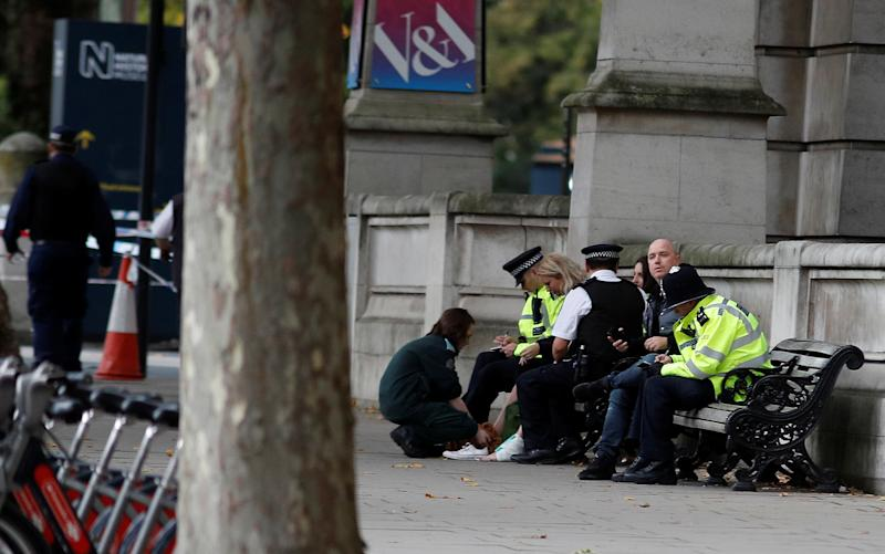 <strong>Police officers stand next to a person with a bandaged ankle</strong> (Peter Nicholls / Reuters)