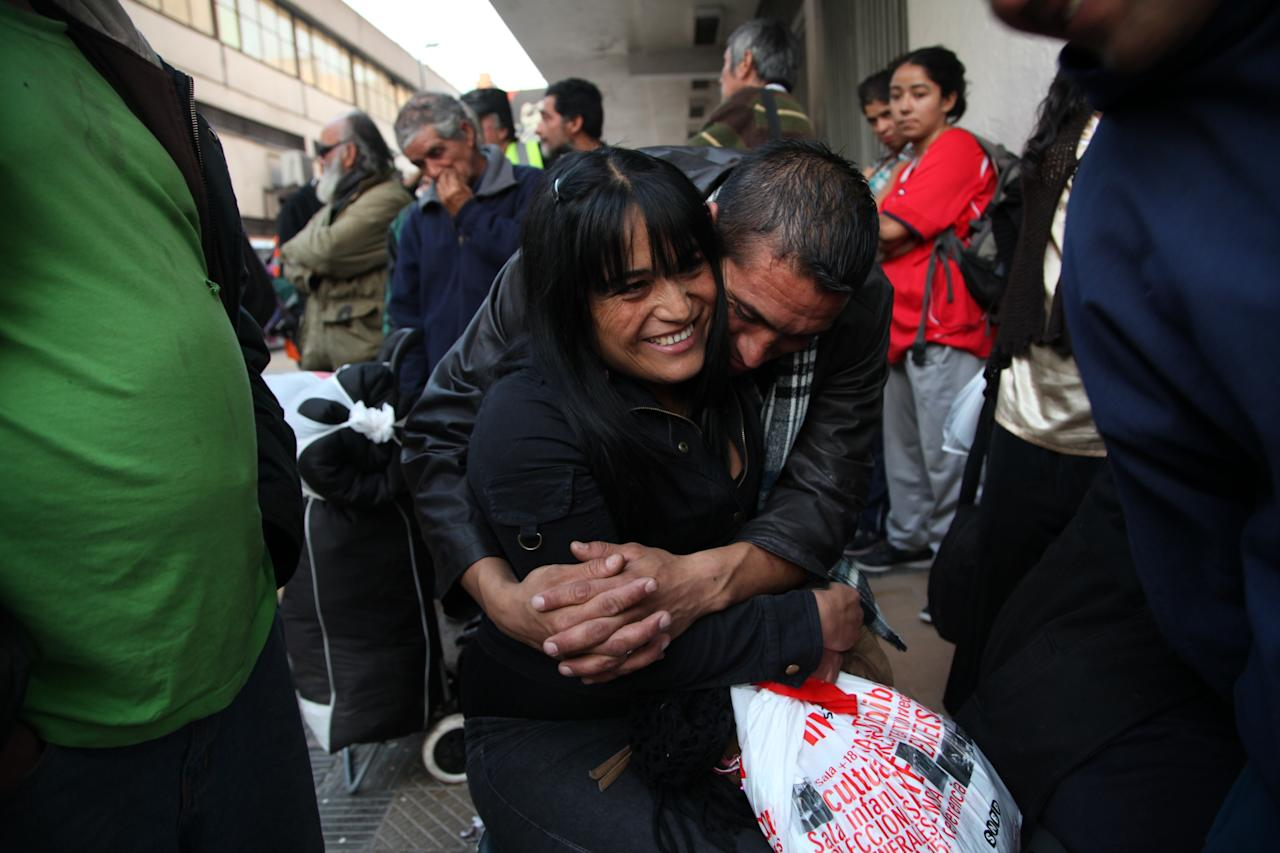 In this May 24, 2013 photo, Jonathan Fuentes hugs his girlfriend Vivian Alvarez as they wait for the shelter to open for the evening at the indoor stadium Estadio Victor Jara which opens its doors to the homeless for winter in Santiago, Chile. The stadium, which opened its doors on May 15 as a temporary shelter to house people throughout the winter who normally sleep on the streets, is where Chilean folksinger Victor Jara was tortured and killed in 1973, just days after Chile's bloody 1973 military coup. Today the stadium is named after him and is Chile's largest homeless shelter. (AP Photo/Brittany Peterson)