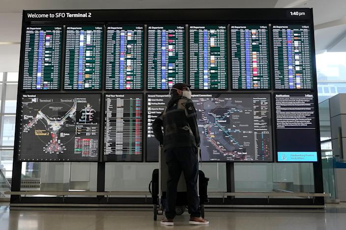 A traveller stands in front of a flight information board at San Francisco International Airport during the coronavirus pandemic in San Francisco, Tuesday, Dec. 22, 2020.