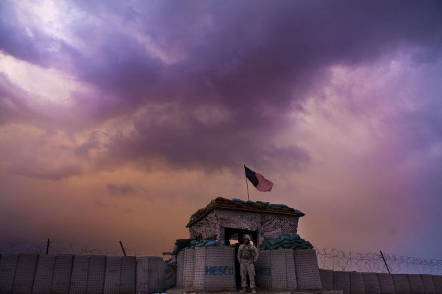 <p>A U.S. Marine from the First Battalion Eighth Marines Alpha Company looks out as an evening storm gathers above an outpost near Kunjak in southern Afghanistan's Helmand province, Feb. 22, 2011. (Photo: Finbarr O'Reilly/Reuters) </p>