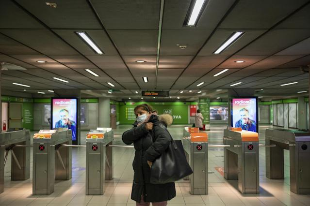 A commuter, wearing a protective face mask, walks through the Garibaldi Milan Metro interchange station in Milan, Italy, on Tuesday, March 10, 2020. (Credit: Camilla Cerea/Bloomberg)