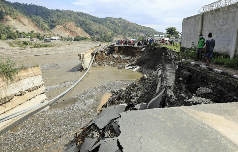 People gather near a damaged road in the aftermath of floods in Dili, East Timor, also known as Timor Leste.