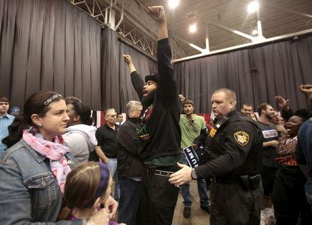 An anti-Trump protester is escorted out of the arena during a campaign rally for Republican U.S. presidential candidate Donald Trump in Cleveland, Ohio, March 12, 2016. REUTERS/Rebecca Cook