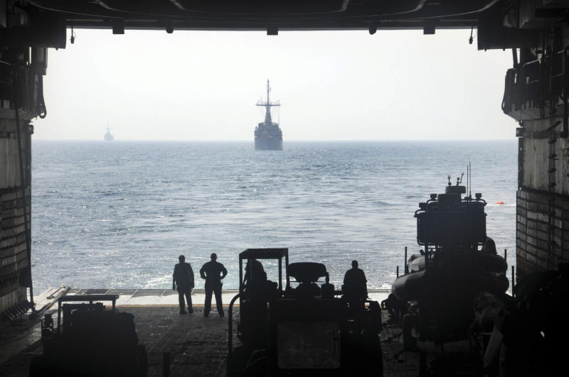 A photo provided by the U.S. Navy, 5th Fleet and dated Aug. 29, 2012, shows Military Sealift Command civilian mariners aboard USS Ponce observing mine countermeasure ships USS Sentry and USS Devastator from the well deck during an astern replenishment-at-sea. The United States and more than two dozen allies are gearing up for the largest naval exercises ever in the Middle East focused on countering the threat of anti-ship mines.(AP Photo/U.S. Navy ,Toni Burton)