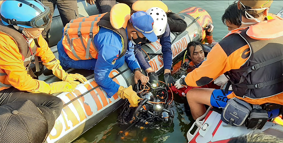 Rescuers recover items from the water.