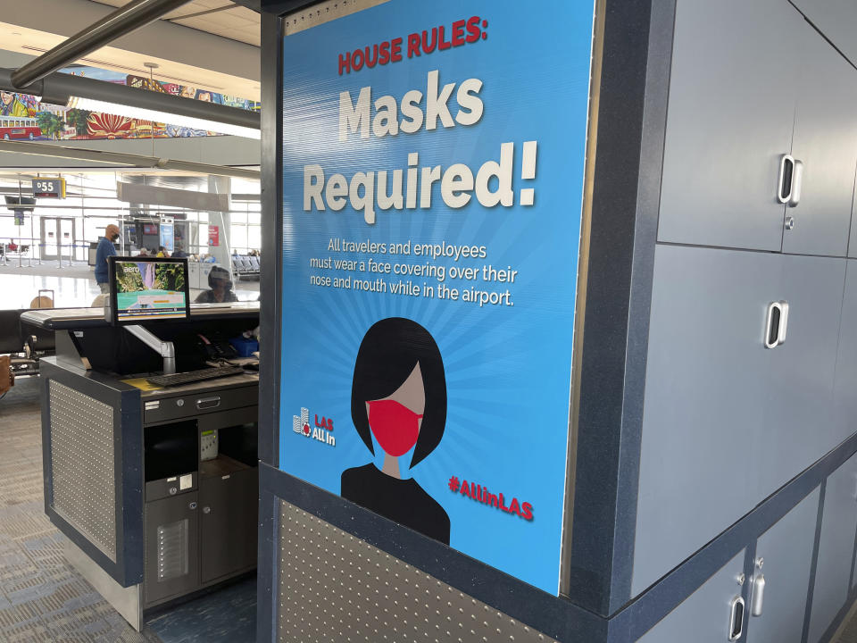 Posters at McCarran Airport in Las Vegas last Friday informed passengers that masks should be worn. (STAR MAX/IPx via AP)