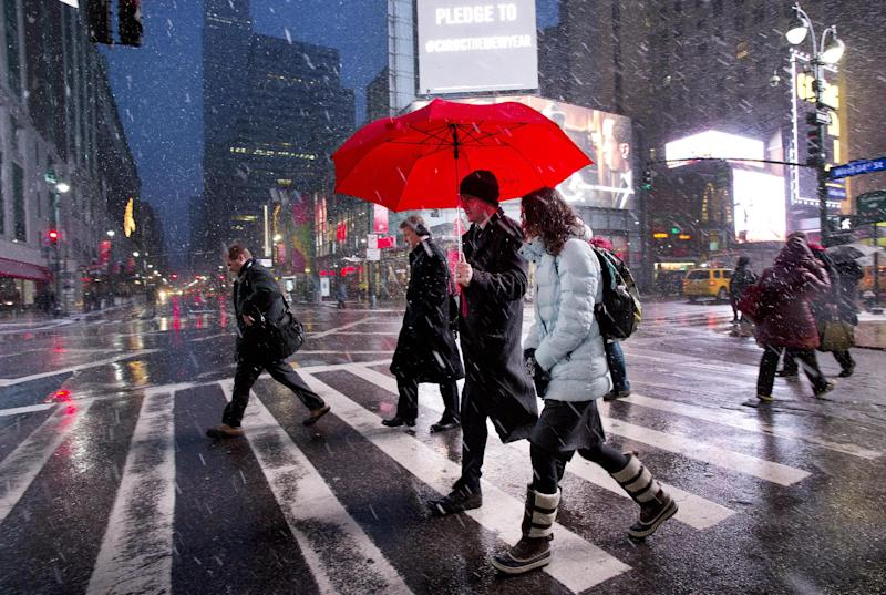 Pedestrians cross a Manhattan street during a light snowfall, Tuesday, Dec. 17, 2013 in New York. The National Weather Service is predicting another 2 to 4 inches of snow for New York City. (AP Photo/Mark Lennihan)