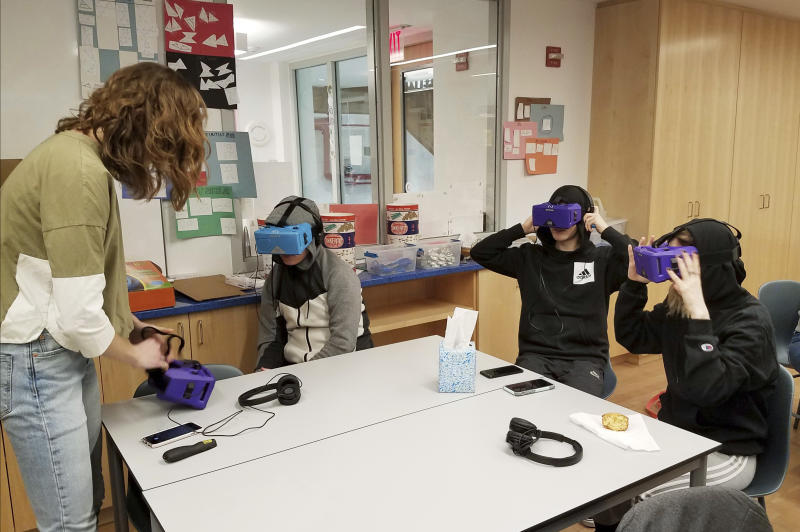 In this Feb. 7, 2018 photo, Lily Adler, left, advisor and teacher at the Berkeley Carroll School in the Brooklyn borough of New York, adjusts her virtuality reality headset. Experts say the technology is still relatively rare in schools, but they expect that to change as costs come down and content improves. From center left are students, Daniel Cornicello, 17, Charlie Hertz, 17, and Taylor Engler, 16. (AP Photo/Deepti Hajela)