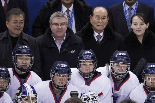 South Korean President Moon Jae-in, IOC president Thomas Bach, North Korea's nominal head of state Kim Yong Nam and Kim Yo Jong, sister of North Korean leader Kim Jong Un, pose for photos with players of the unified Korea team. (AP)