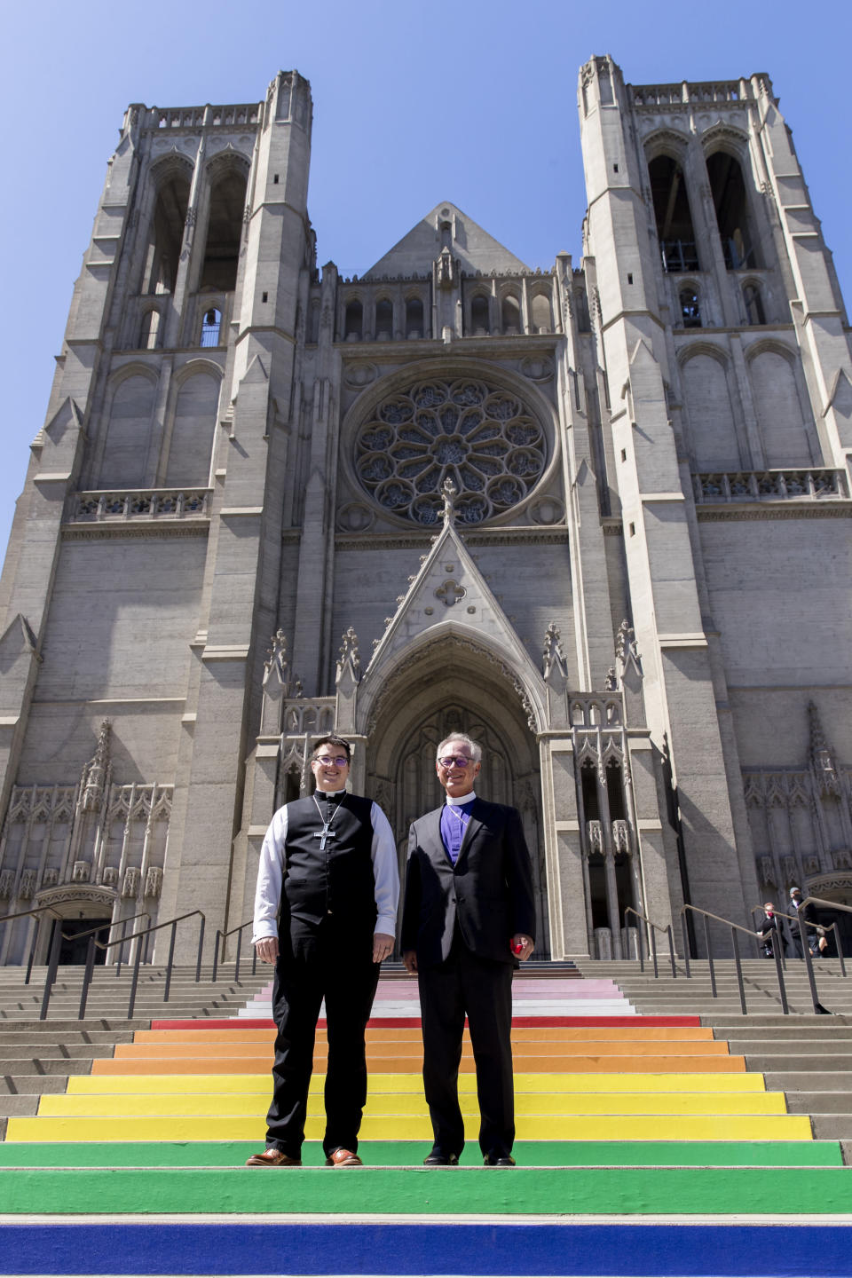 Bishop Megan Rohrer, left, and Bishop Marc Andrus stand on the rainbow steps before Bishop Rohrer's installation ceremony at Grace Cathedral in San Francisco, Saturday, Sept. 11, 2021. Rohrer is the first openly transgender person elected as bishop in the Evangelical Lutheran Church of America. (AP Photo/John Hefti)