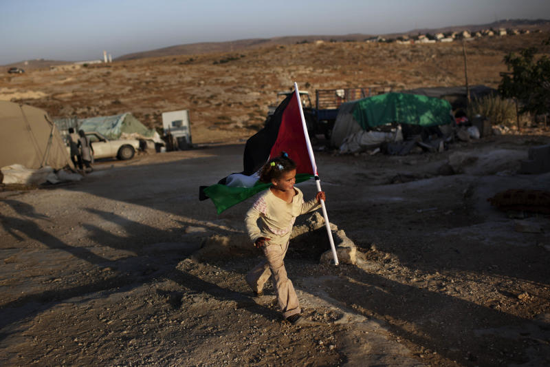 In this Friday, June 15, 2012 photo, a Palestinian girls carries a Palestinian flag in the West Bank town of Susiya. Palestinian herders in this hamlet have clung to arid acres spread over several West Bank hills for decades, even as Israel forced them to live off the grid while providing water and electricity to nearby Jewish settlements and unauthorized outposts. But the end seems near for Susiya's 200 residents: Citing zoning violations, Israel is threatening to demolish the village, including German-funded solar panels.  (AP Photo/Bernat Armangue)
