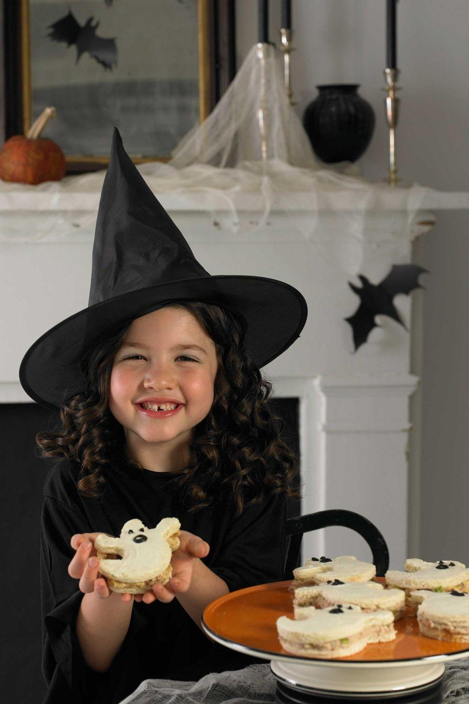 """<p>To create these friendly apparitions, simply cut through white bread with a ghost-shaped cookie cutter and spread some chicken salad between two slices. Add a thin layer of cream cheese to the top first then decorate with olive slices.</p><p><em><a href=""""https://www.womansday.com/food-recipes/food-drinks/recipes/a9993/little-ghost-sandwiches-recipe-121372/"""" rel=""""nofollow noopener"""" target=""""_blank"""" data-ylk=""""slk:Get the Ghost Sandwiches recipe."""" class=""""link rapid-noclick-resp"""">Get the Ghost Sandwiches recipe.</a></em> </p>"""