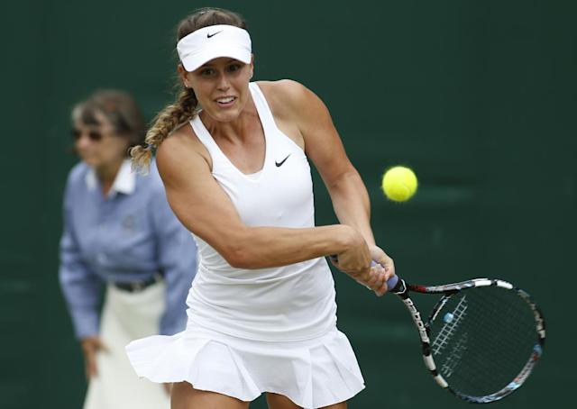 Michelle Larcher De Brito of Portugal plays a return to Svetlana Kuznetsova of Russia during their first round match at the All England Lawn Tennis Championships in Wimbledon, London, Tuesday, June 24, 2014. (AP Photo/Alastair Grant)