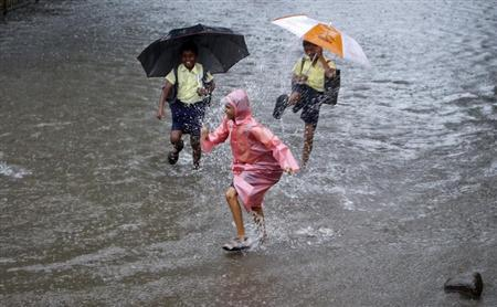 School children play on a flooded street during heavy monsoon rains in Mumbai